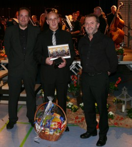 Seit einem Jahrzehnt hält er den Taktstock in der Hand: Oliver Bickel (Mitte), der das Große Blasorchester des Musikvereins Bauschlott in die Höchststufe (Stufe 5, sehr schwer) führte. Dafür dankten ihm der Vorsitzende Stefan Weihing (links) und sein  Vize Andreas Stößer (rechts). Foto: Dietrich